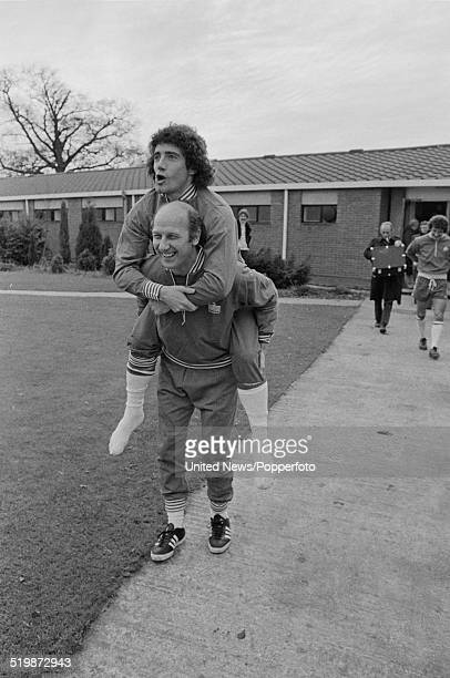 Hamburg and England footballer Kevin Keegan is carried by a member of the coaching staff during an England team training session at London Colney in...