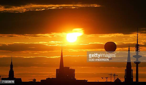 A hot air ballon descends as the sun sets behind the city skyline of Hamburglate 28 June 2006 Portugal and England will meet in the northern Germany...