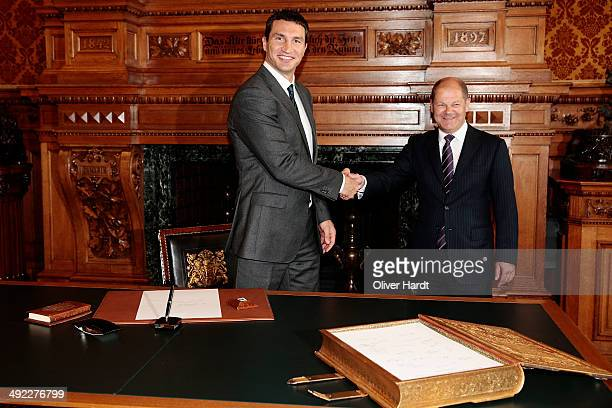 Hamburg mayor Olaf Scholz shakes hands with Wladimir Klitschko after Klitschko signed the Golden Book of Hamburg during their visit of the city...