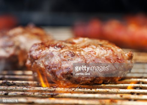 Hamburger and Flames on Barbeque Grill : Stock Photo