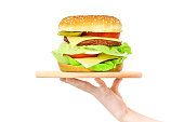 Concept of food serving service - female hand holding a wooden board with a big hamburger on a white background (mixed)