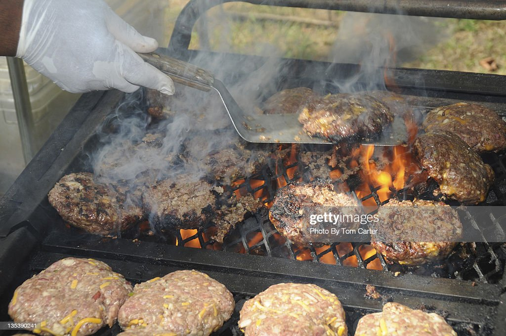 Hamburgers and cheeseburgers being grilled : Stock Photo