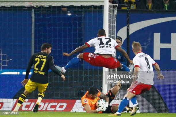 Hamburg's Brazilian midfielder Walace jumps over Dortmund's Swiss goalkeeper Roman Buerki during the German first division Bundesliga football match...