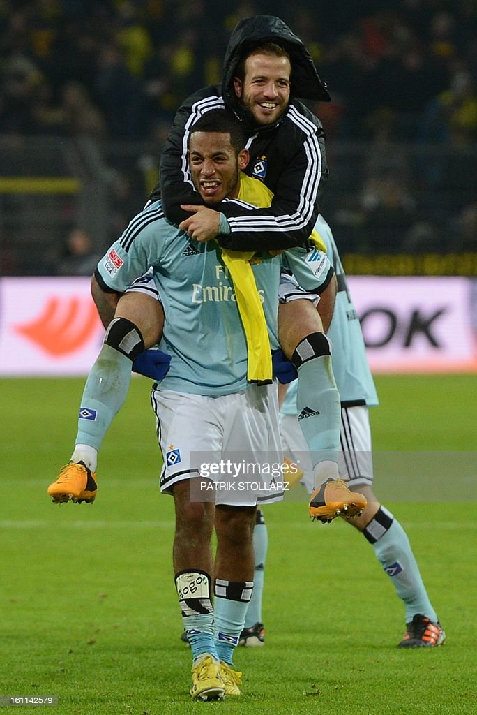 Hamburg's defender Dennis Aogo and Hamburg's Dutch midfielder Rafael van der Vaart celebrate after the German first division Bundesliga football match Borussia Dortmund vs Hamburger SV in the German city of Dortmund on February 9, 2013. Hamburg won 1-4. DFL rules to limit the Onlines usage during matchtime to 15 pictures per match. Image sequences to simulate video is not allowed at any time. For further queries please contact DFL directly at + 49 69 650050.