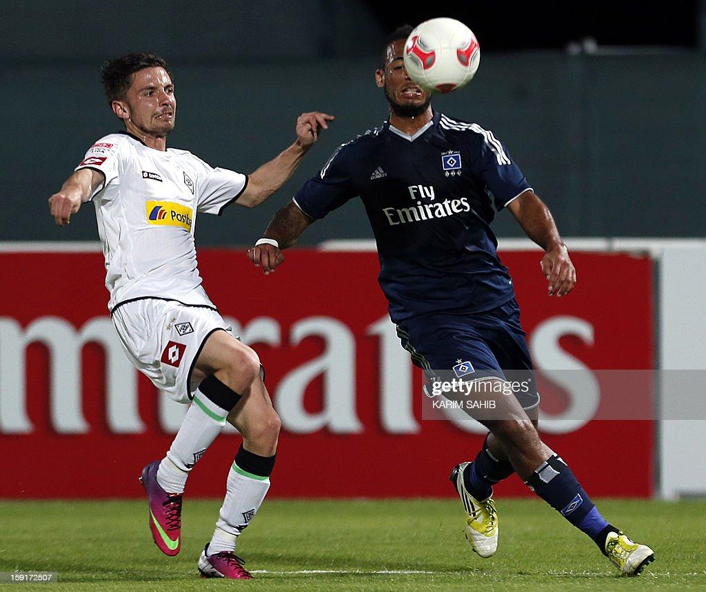 Hamburg's defender Dennis Aogo (R) challenges Borussia Monchengladbach's midfielder Julian Korb during their friendly football match in the Gulf emirate of Dubai on January 9, 2013.