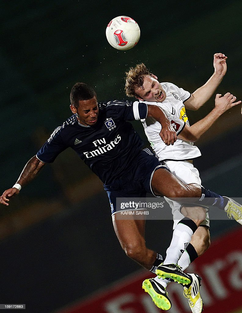 Hamburg's defender Dennis Aogo (L) jumps to head the ball with Borussia Monchengladbach's midfielder Tony Jantschke during their friendly football match in the Gulf emirate of Dubai on January 9, 2013.