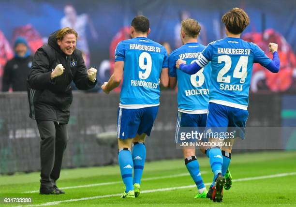 Hamburg's head coach Markus Gisdol celebrates with Hamburg's Greek defender Kyriakos Papadopoulos and Hamburg's midfielder Lewis Harry Holtby after...
