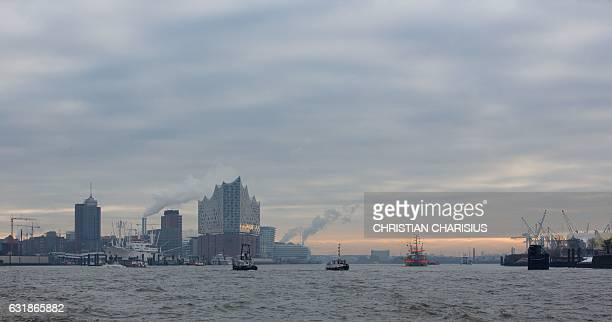 Hamburg's new concert house the Elbphilharmonie is seen behind ships navigating on the river Elbe in Hamburg northern Germany on January 17 2017 /...