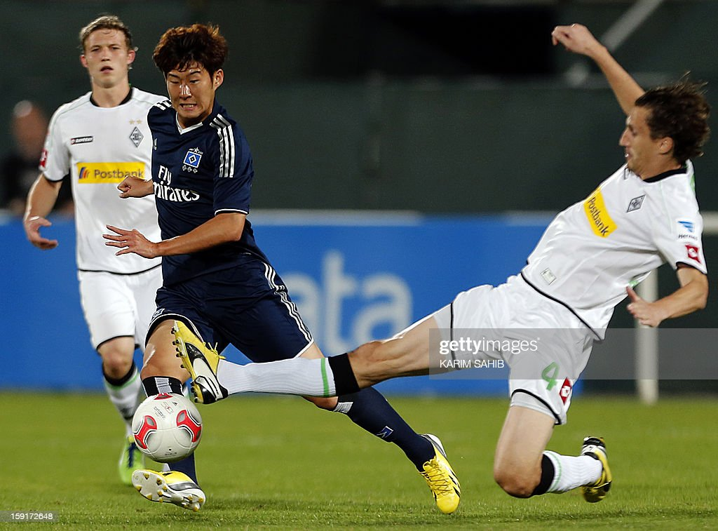 Hamburg's striker Son Heung-Min (L) is challenged by Borussia Monchengladbach's defender Roel Brouwers during their friendly football match in the Gulf emirate of Dubai on January 9, 2013.