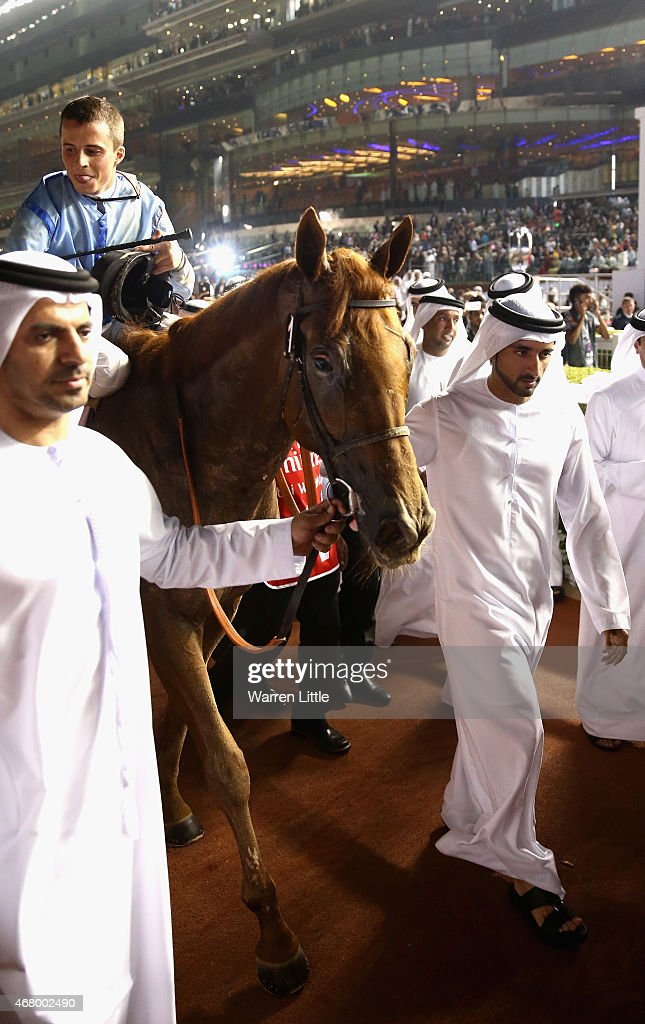 Hamdan bin Mohammed bin Rashid Al Maktoum, Crown Prince of Dubai and Godolphin trainer Saeed bin Suroor lead Prince Bishop into the winner enclosure after winning the Dubai World Cup at the Meydan Racecourse on March 28, 2015 in Dubai, United Arab Emirates.