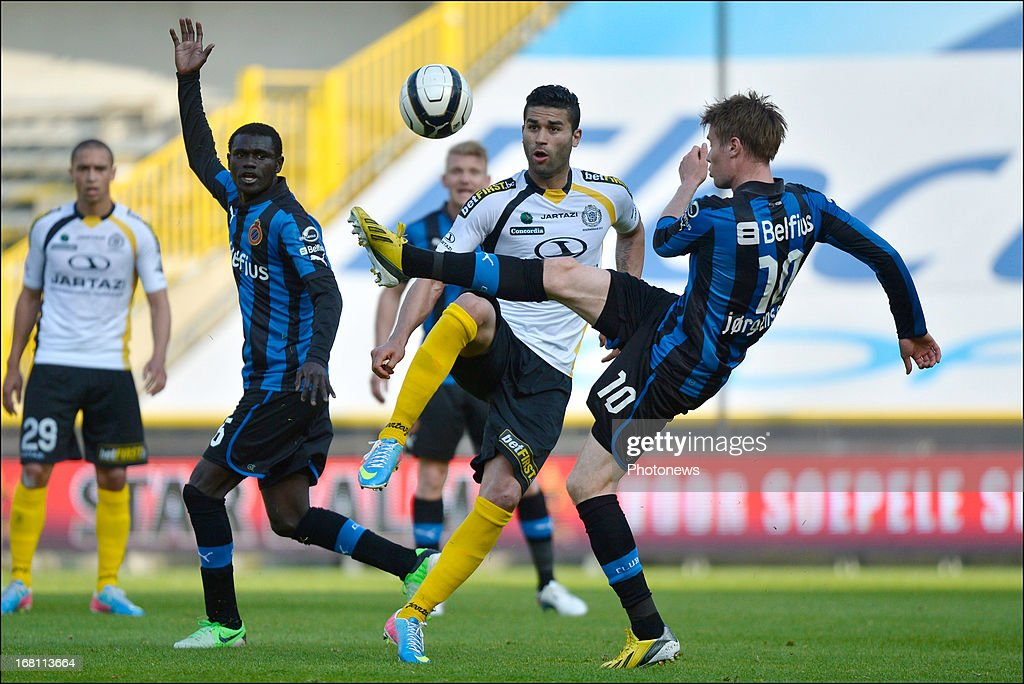 Hamdi Harbaoui of Sporting Lokeren OVL (2nd R ) battles for the ball with Jesper Jorgensen of Club Brugge KV during the Jupiler Pro League play-off 1 match between Club Brugge and Sporting Lokeren on May 5, 2013 in Brugge, Belgium.