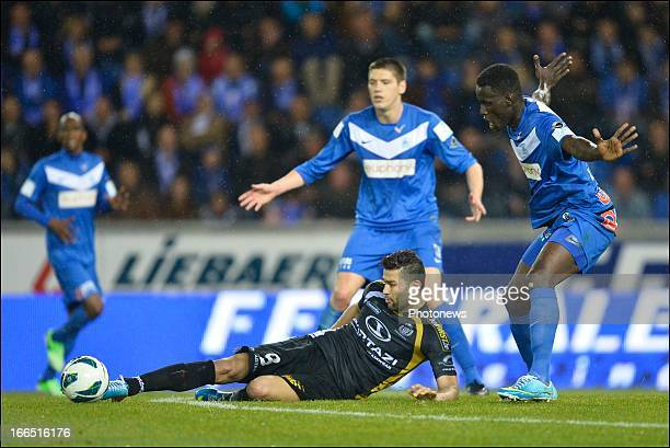 Hamdi Harbaoui of Sporting Lokeren OVL lies the ground in front of Kara Mbodj of KRC Genk during the Jupiler League Play off match between KRC Genk...
