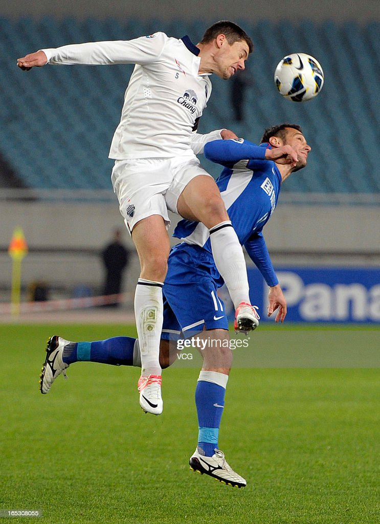Hamdi Salihi #11 of Jiangsu Sainty and Osmar Barba #5 of Buriram United battle for the ball during the AFC Champions League match between Jiangsu Sainty and Buriram United at Nanjing Olympic Sports Center Stadium on April 2, 2013 in Nanjing, China.