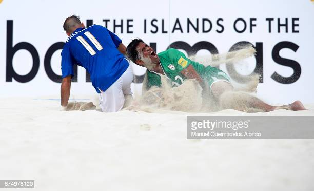 Hamid Behzadpour of Iran is tackled by Paolo Palmacci of Italy during the FIFA Beach Soccer World Cup Bahamas 2017 group B match between Italy and...