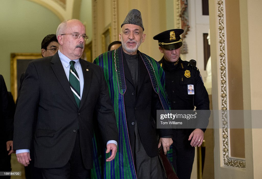 Hamid Karzai, President of Afghanistan, makes his way through the Oho Clock Corridor in the Capitol with Senate Sergeant at Arms Terry Gainer, en route to a meeting with Senate Minority Leader Mitch McConnell, R-K.Y., Sen. Bob Casey, D-Pa., Sen. Deb Fischer, R-Neb., and Sen. Tim Kaine, D-Va.