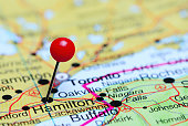 Photo of pinned Hamilton on a map of Canada. May be used as illustration for traveling theme.