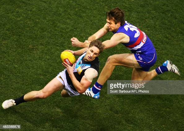 Hamish Hartlett of Port Adelaide is tackled during the round 19 AFL match between the Western Bulldogs and Port Adelaide Power at Etihad Stadium on...