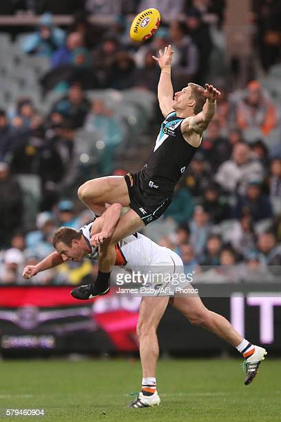 Hamish Hartlett of the Power flies over Steve Johnson of the Giants during the 2016 AFL Round 18 match between Port Adelaide Power and the GWS Giants...