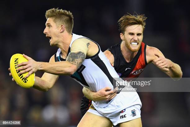 Hamish Hartlett of the Power is tackled by James Stewart of the Bombers during the round 12 AFL match between the Essendon Bombers and the Port...