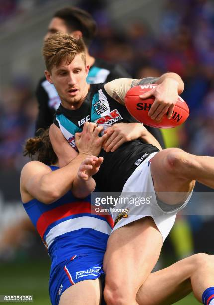 Hamish Hartlett of the Power is tackled by Marcus Bontempelli of the Bulldogs during the round 22 AFL match between the Western Bulldogs and the Port...