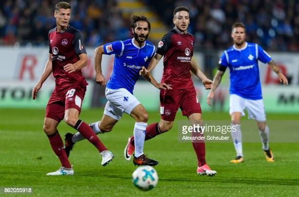 Hamit Altintop of Darmstadt in action against Patrick Erras of Nuernberg and Kevin Moehwald of Nuernberg during the Second Bundesliga match between...