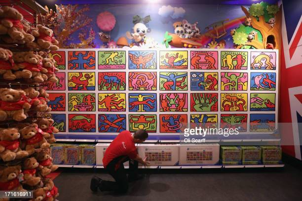 Hamleys employee adjusts a box for the 32256piece Keith Haring jigsaw beneath the completed puzzle in Hamleys toy shop on June 27 2013 in London...