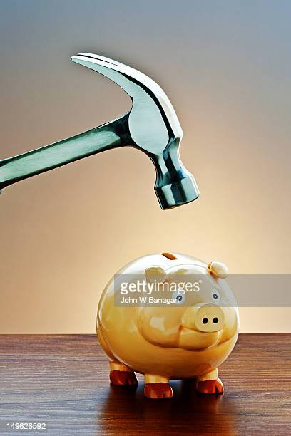 Hammer about to smash a piggy bank