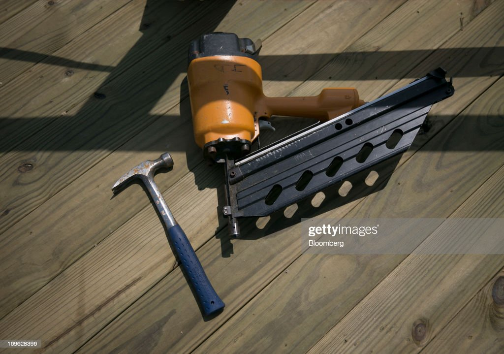 A hammer and pneumatic nailer sit on the boardwalk in Seaside Heights, New Jersey, U.S., on Wednesday, May 29, 2013. Sandy, which came ashore near Atlantic City, killed dozens of people and destroyed more than 365,000 homes in the state. Christie has said it will cost $36.9 billion for repairs and to prevent devastation from future storms. Photographer: Scott Eells/Bloomberg via Getty Images