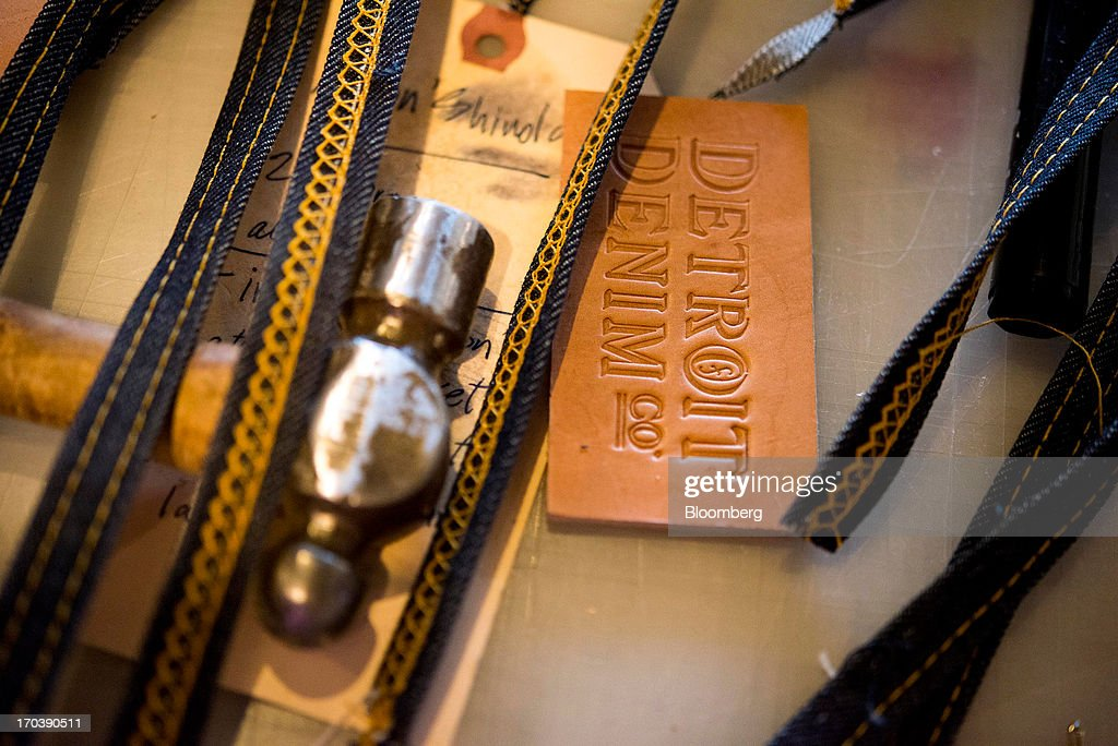 A hammer, denim purse straps and a Detroit Denim leather tag sit on a table at Detroit Denim, in Detroit, Michigan, U.S., on Wednesday, June 12, 2013. The Commerce Department is scheduled to release monthly business inventories data on June 13. Photographer: Ty Wright/Bloomberg via Getty Images