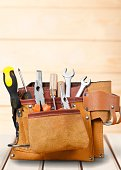 Tool belt with tools on wooden desk
