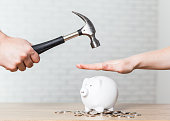 A hand holding a hammer which is raised above a white piggy bank