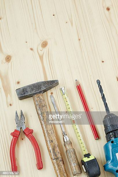 Hammer, screwdriver, pencil, drill, measuring tape, hammer, plier on wood, close up