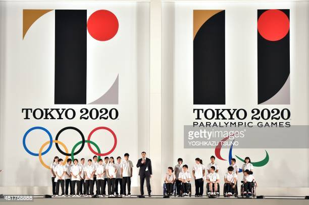 Hammer throw gold medalist Koji Murofushi accompanied by young athletes delivers a speech as the logo marks of the Tokyo 2020 Olympic and Paralympic...