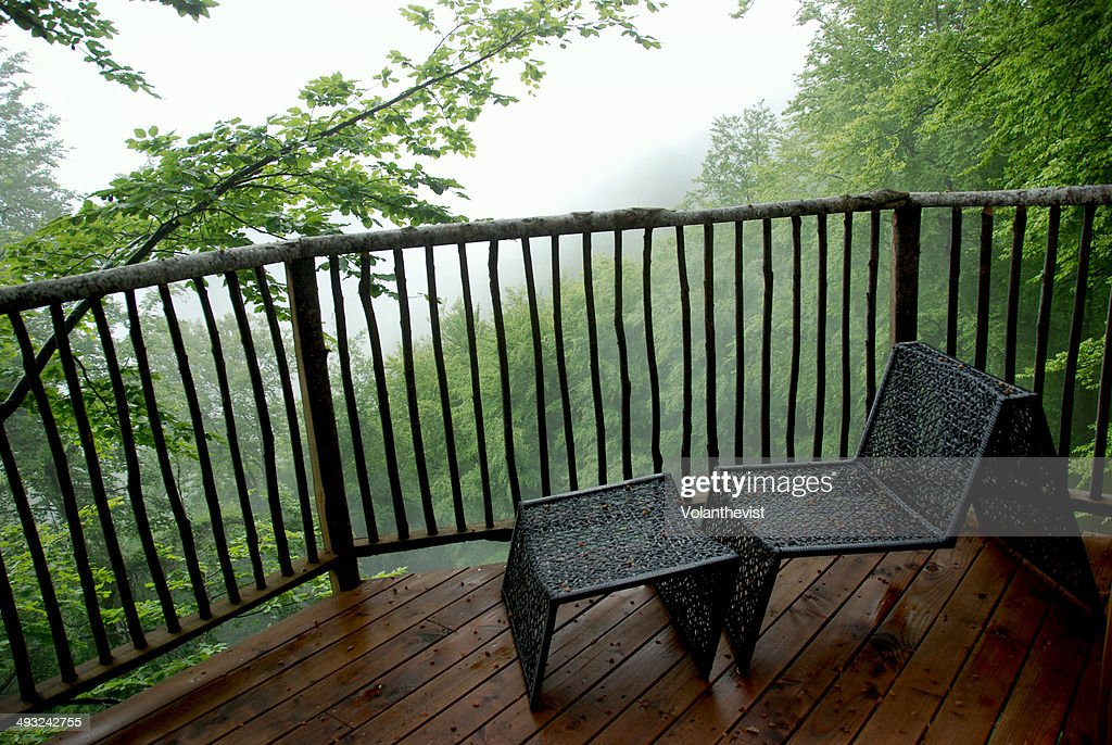 Hammock on a wooden balcony overlooking the forest stock for Balcony hammock