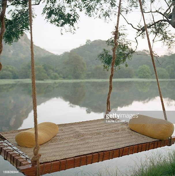 Hammock on tree by still rural lake