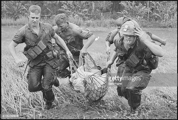 HammockStretcher Saigon Four troopers of the US 9th Division use a rope hammock to rush a wounded civilian through swampland to a waiting helicopter...