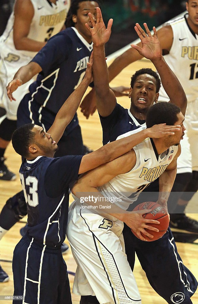 J Hammons of the Purdue Boilermakers is trapped by Shep Garner and Jordan Dickerson of the Penn State Nittany Lions during the quarterfinal round of...