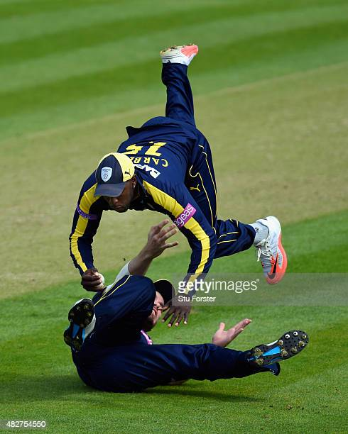 Hampshire fielder Michael Carberry takes a catch to dismiss Glamorgan batsman Aneurin Donald despite the attentions of his team mate Joe Gatting...