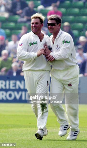 Hampshire spinner Shane Warne celebrates with his captain Robin Smith after taking the wicket of Glamorgan's Steve James during the Benson Hedges...