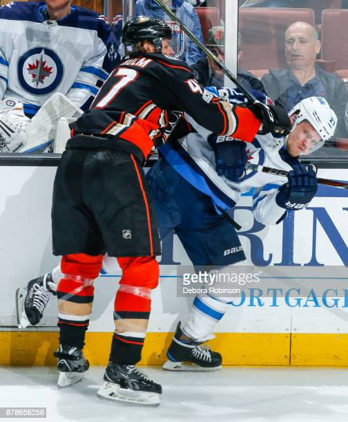 Hampus Lindholm of the Anaheim Ducks checks Nikolaj Ehlers of the Winnipeg Jets during the third period of the game at Honda Center on November 24...