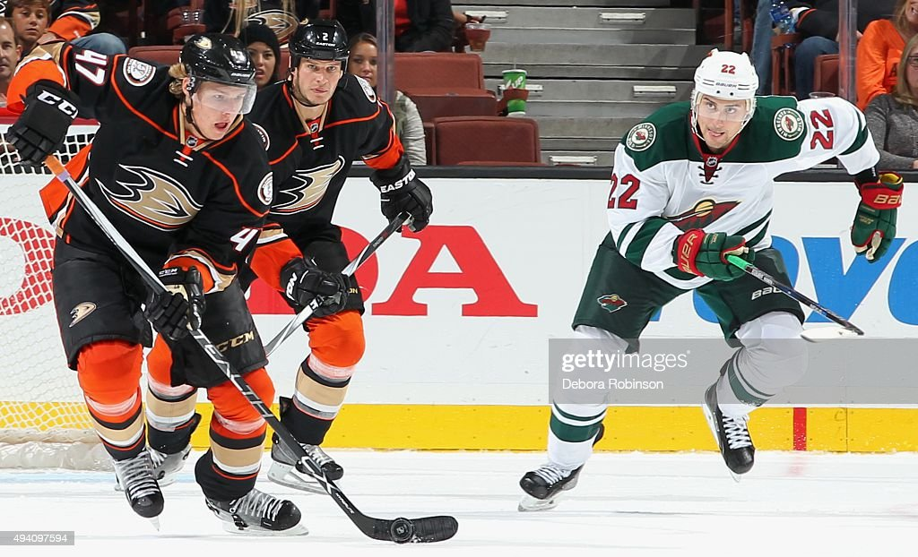 Hampus Lindholm of the Anaheim Ducks controls the puck against Nino Niederreiter of the Minnesota Wild on October 18 2015 at Honda Center in Anaheim...