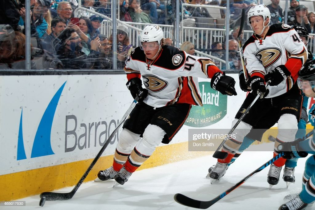 Hampus Lindholm #47 of the Anaheim Ducks moves the puck along the boards as Josh Mason #42 of the Anaheim Ducks looks during a NHL game against the Anaheim Ducks at SAP Center at San Jose on March 18, 2017 in San Jose, California.