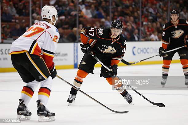 Hampus Lindholm of the Anaheim Ducks shoots the puck as Dougie Hamilton of the Calgary Flames defends during the first period of a game at Honda...