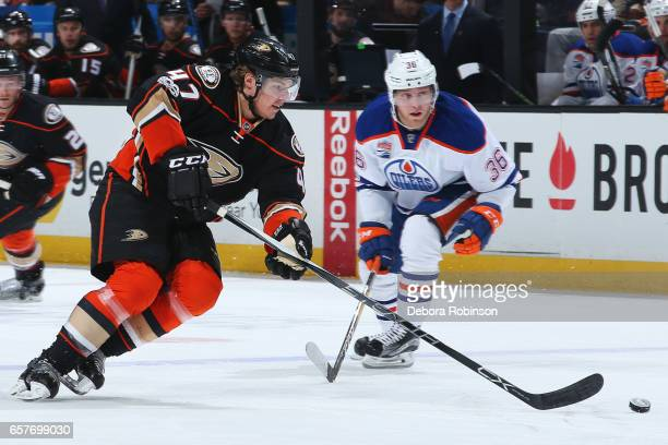 Hampus Lindholm of the Anaheim Ducks skates with the puck against Drake Caggiula of the Edmonton Oilers during the game on March 22 2017 at Honda...