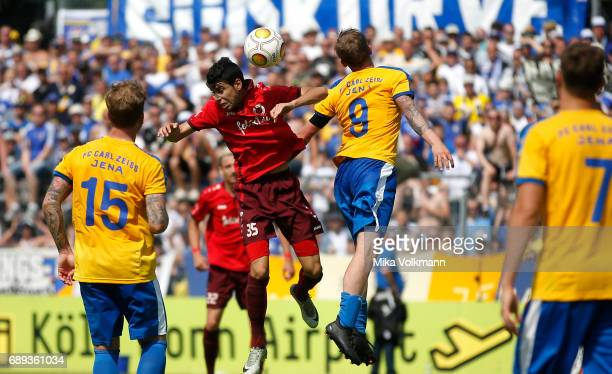 Hamza Saghiri of Viktoria Koeln jumps for a header against Rene Eckardt of Jena during the Third League Plaffoff match between Viktoria Koeln and FC...