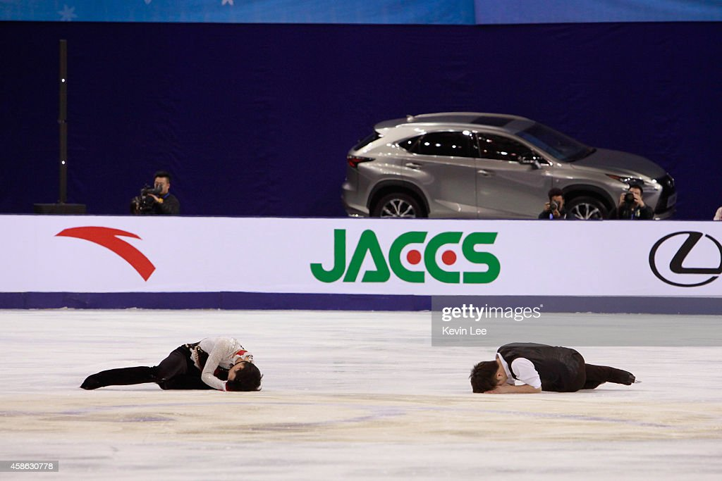 Han Yan of China and (L) Yuzuru Hanyu of Japanlie on the course after collision at warm up period in Men Free Skating during the Lexus Cup of China 2014 on November 8, 2014 in Shanghai, China.