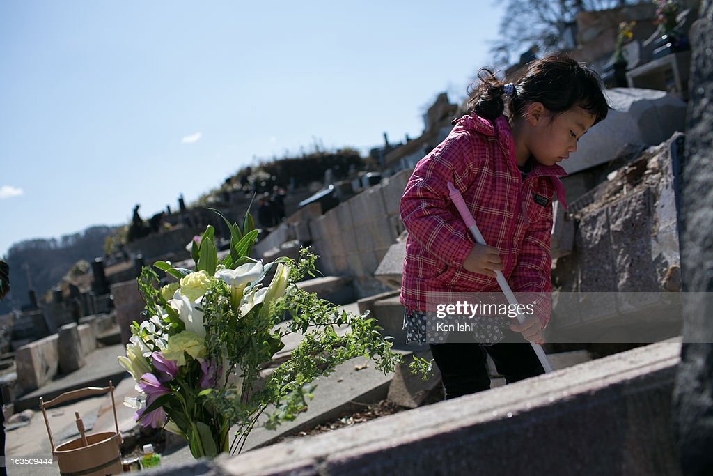 Hana Tanaka, 4, cleans the grave of her grandparents, who were killed by the tsunami triggered by the 2011 Magnitude 9.0 earthquake at Kouganji Temple on March 11, 2013 in Otsuchi, Iwate, Japan. On March 11 Japan commemorates the second anniversary of the magnitude 9.0 earthquake and tsunami that claimed more than 18,000 lives.