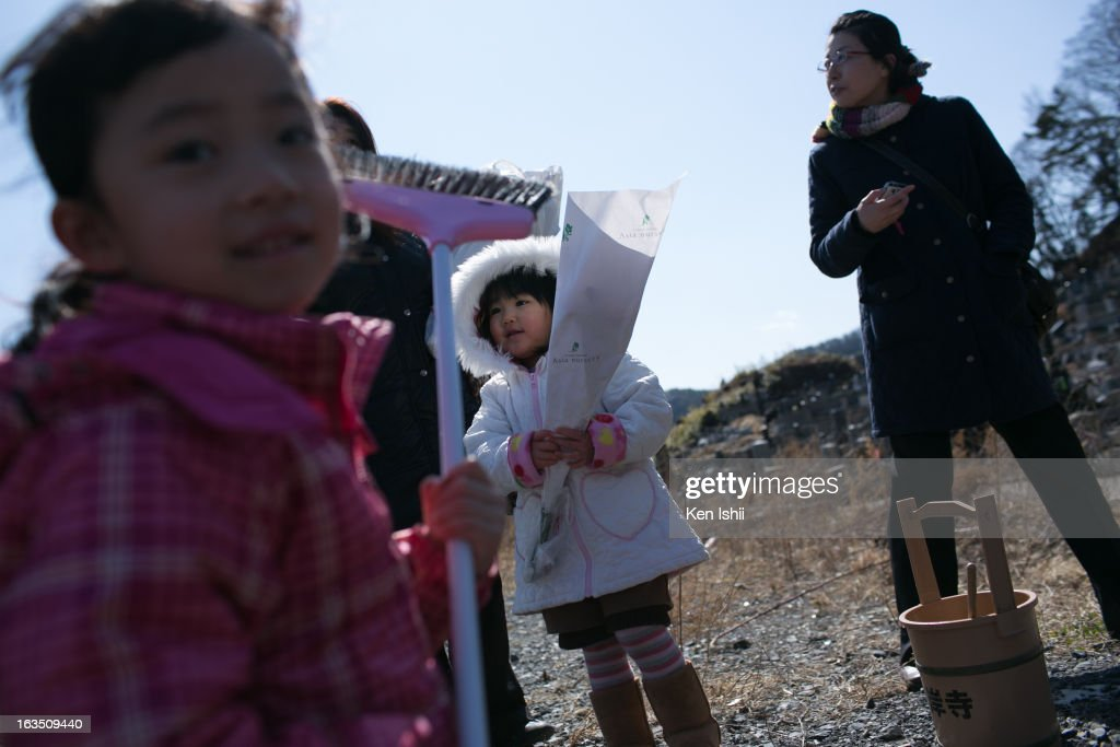 Hana Tanaka (L0, age 4, and her sister Rei, 3, attend a memorial service for their grandparents and other victims of the tsunami at Kouganji temple on March 11, 2013 in Otsuchi, Iwate, Japan. On March 11 Japan commemorates the second anniversary of the magnitude 9.0 earthquake and tsunami that claimed more than 18,000 lives.