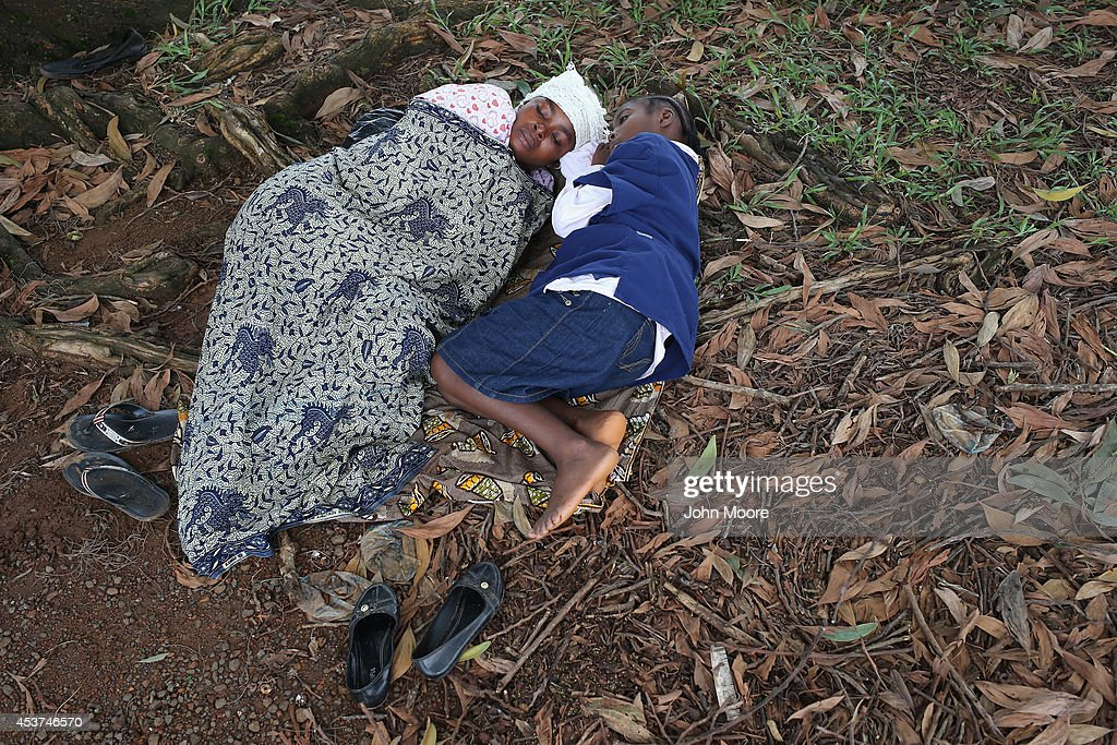 Hanah Siafa lies with her daughter Josephine while hoping to enter the new Doctors Without Borders Ebola treatment center on August 17 2014 in...