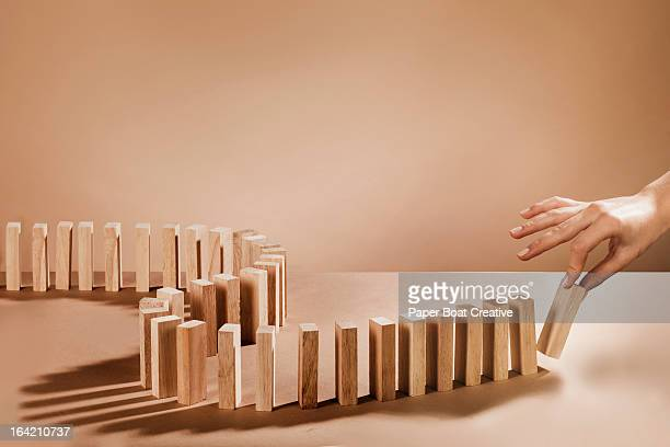 Hand about to knock over dominoes made out of wood